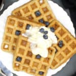 Overhead shot of four vegan waffles on a plate with whipped cream, blueberries and maple syrup