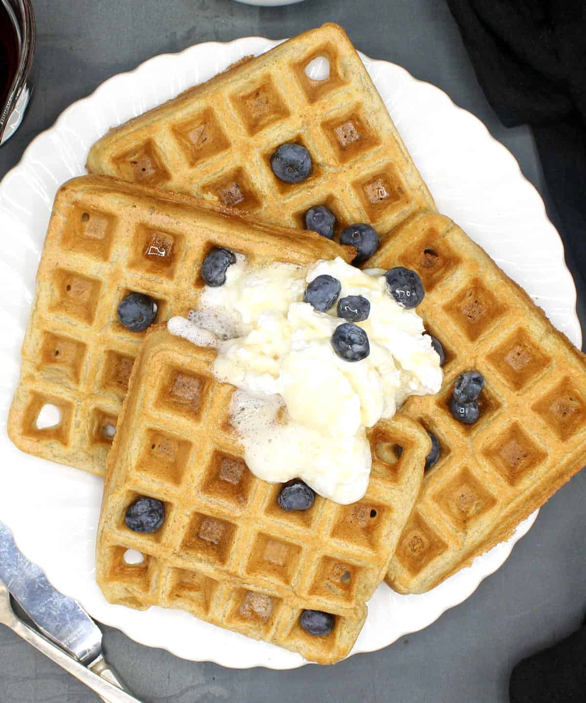 Vegan waffles on a white plate with whipped cream and blueberries.