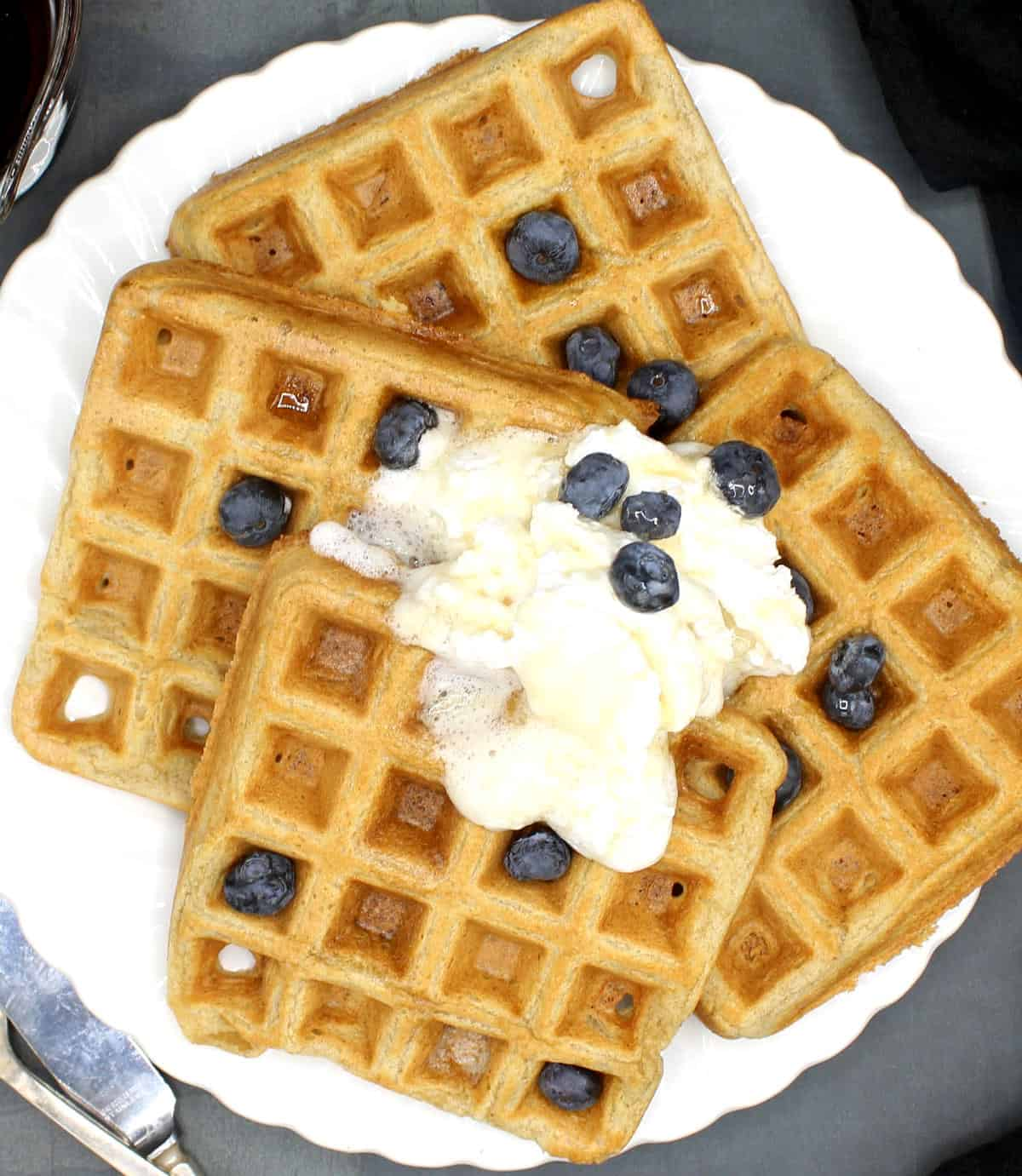 Photo of perfect vegan waffles on a plate with vegan whipped cream and blueberries.