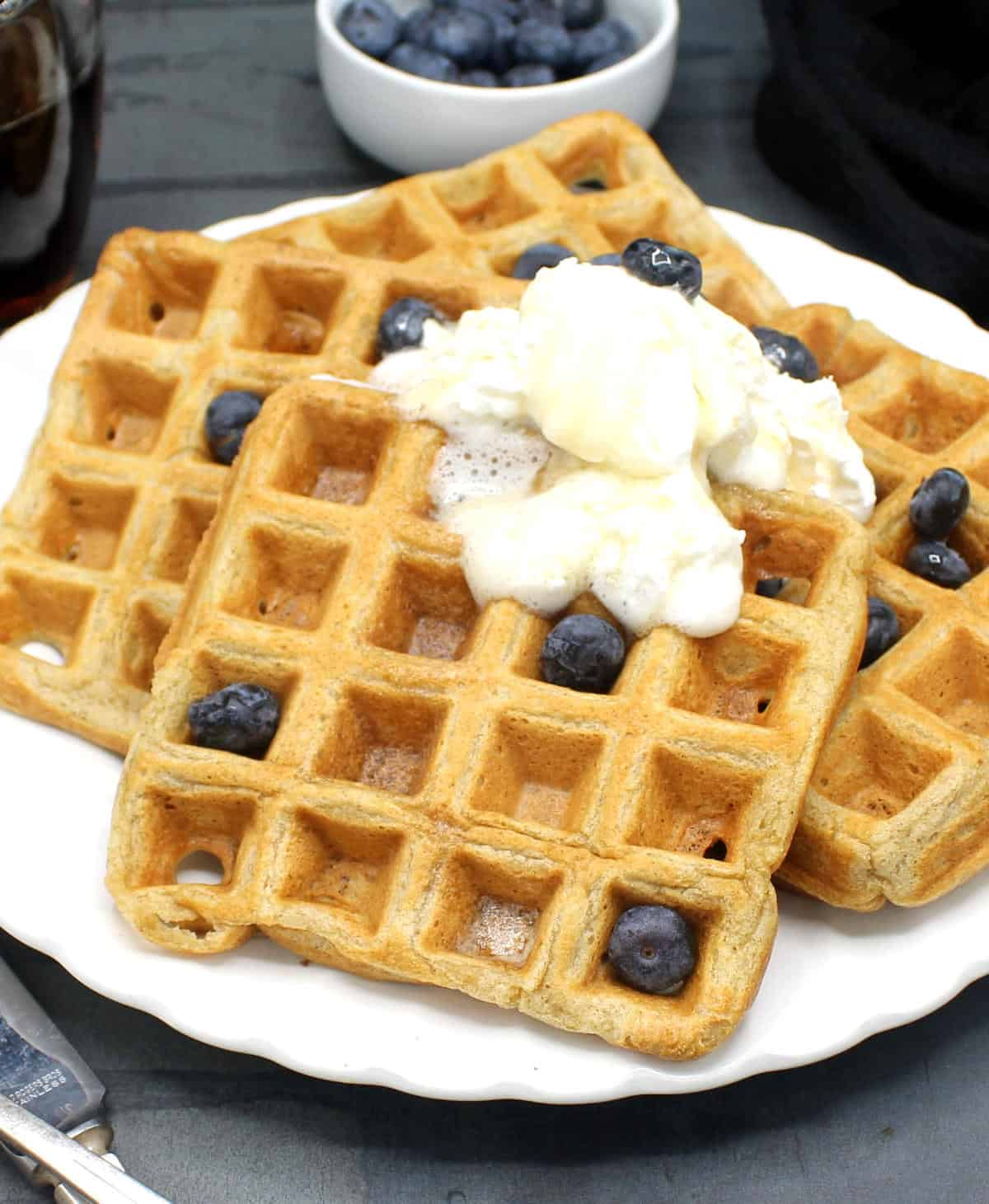 Closeup photo of four vegan waffles on a white plate with vegan whipped cream and blueberries.
