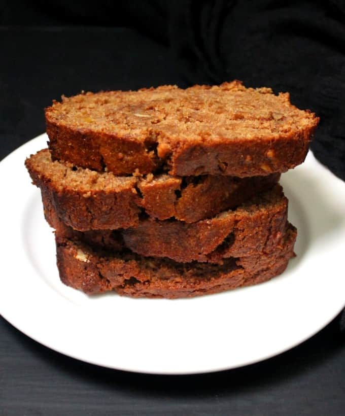 Slices of vegan banana bread stacked in a white plate