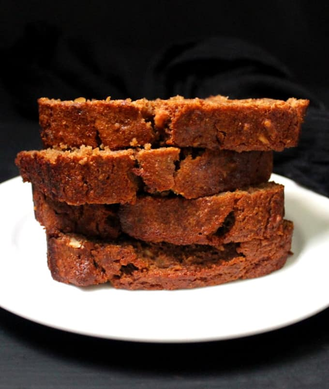 Front shot of four stacked slices of vegan banana bread on a white plate