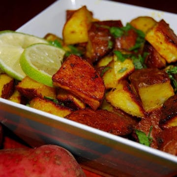 Oven roasted potatoes in a square melamine bowl with slices of lime and cilantro