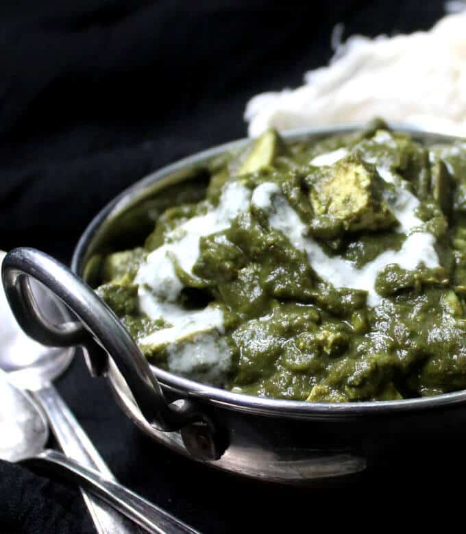 Partial shot of a bowl of vegan palak paneer with cubes of tofu and cashew cream in a steel karahi.
