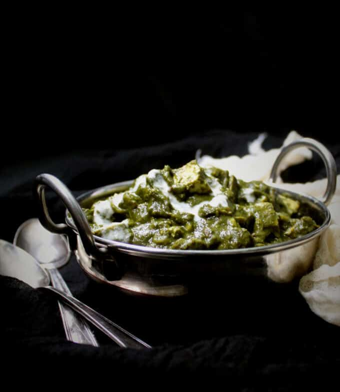 A front partial shot of a bowl of tofu palak paneer with spoons and a cheesecloth on the side