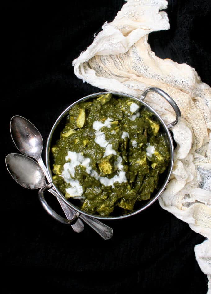 A top shot of green Indian palak tofu paneer with cubes of super firm tofu and an off-white cheesecloth to the side