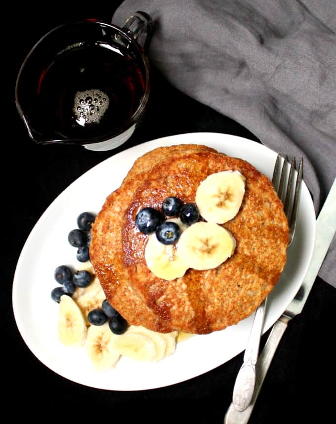Top shot of a stack of golden vegan pancakes in a white oval plate with blueberries and bananas and a fork with maple syrup on the side