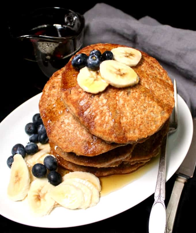 Stack of vegan pancakes made with whole wheat with fruit on a white plate with a fork and knife and maple syrup