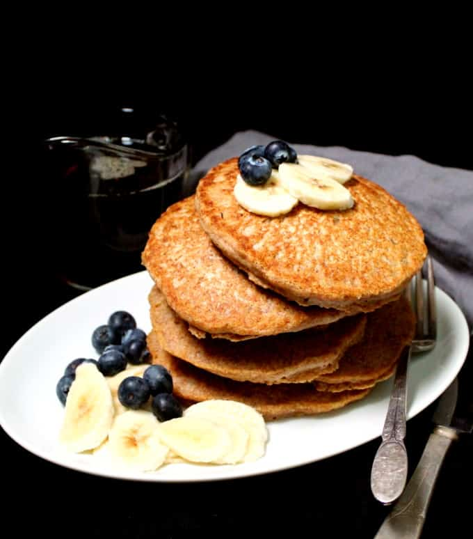 Front shot of a stack of six vegan pancakes with fruit in a white plate with a fork and knife