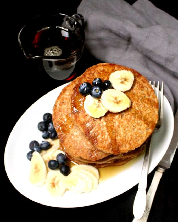 Top shot of vegan pancakes with fruit and maple syrup on a white plate with a knife, fork and gray napkin