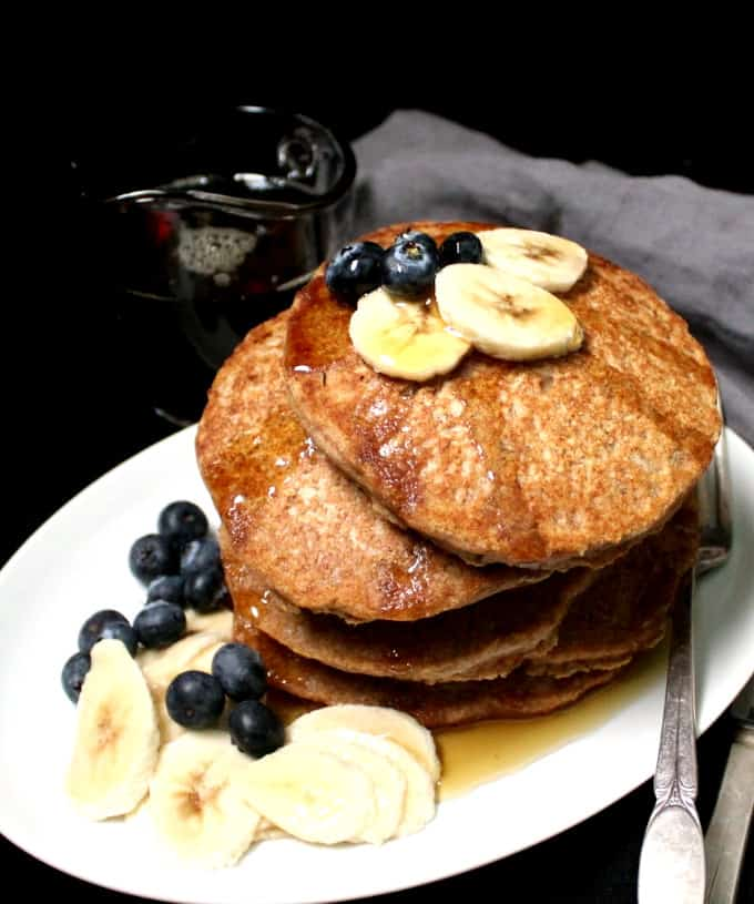 A close shot of six stacked vegan pancakes with fruit and maple syrup in a white plate