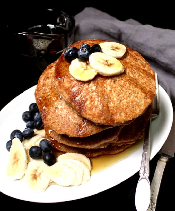 Photo of a stack of fluffy Vegan Whole Wheat Pancakes on a white plate with bananas, blueberries and maple syrup