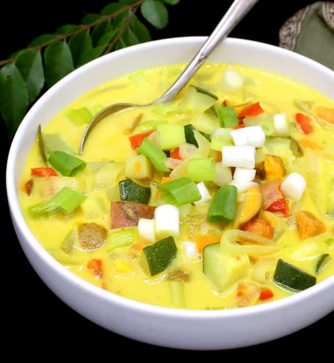 Close up of a white bowl with colorful vegetable moilee with scallions, bell peppers, tomatoes, potatoes, sweet potatoes and zucchini with a spoon and a green napkin and curry leaves