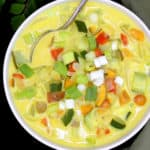 A white bowl with colorful vegetable moilee with scallions, bell peppers, tomatoes, potatoes, sweet potatoes and zucchini with a spoon and a green napkin and curry leaves