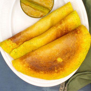 Three adai dosas on a white plate with sambar