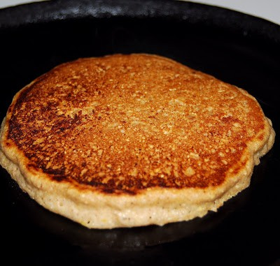 A vegan four-grain pancake cookng in cast iron skillet