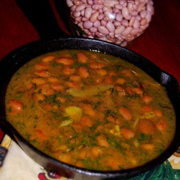 Curried Pink Beans in a skillet with more dry beans in the background