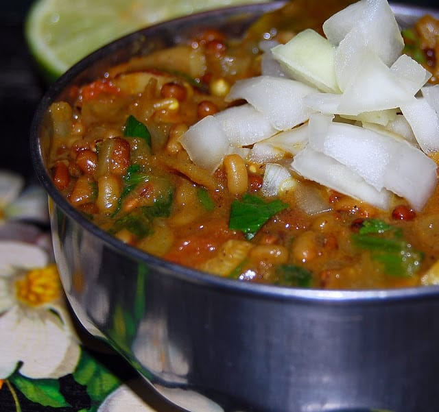 Usal, a spicy Indian bean curry, in a steel bowl with onions and limes