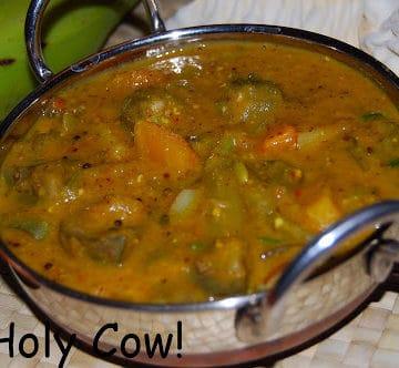 Ezhukari kuzhambu in a steel karahi bowl with cilantro