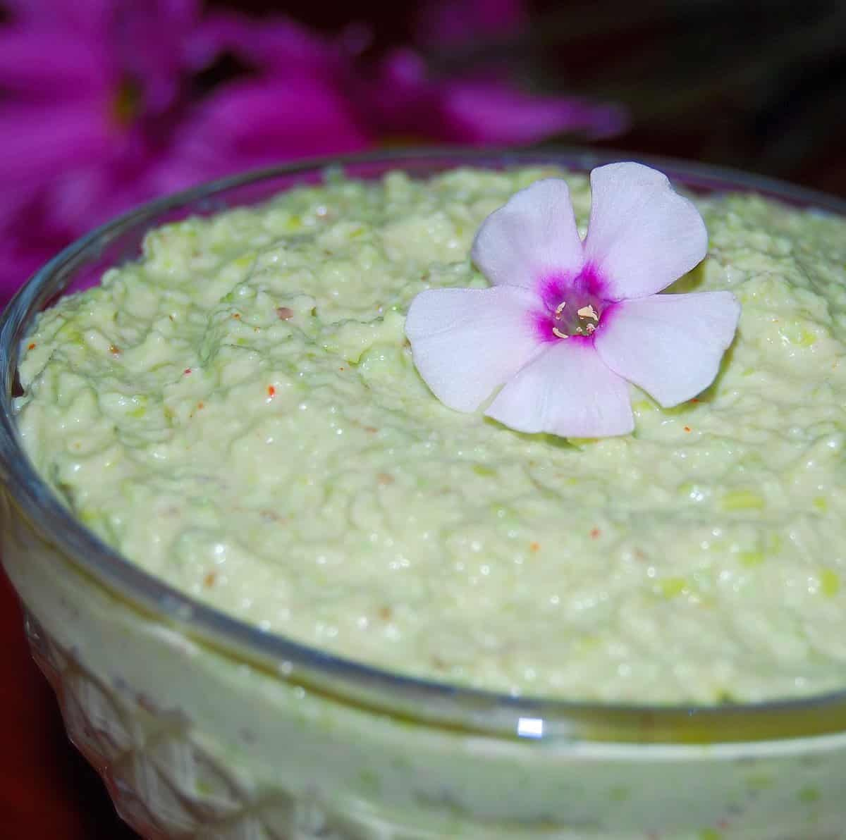 Edamame Hummus in a bowl with a pink flower