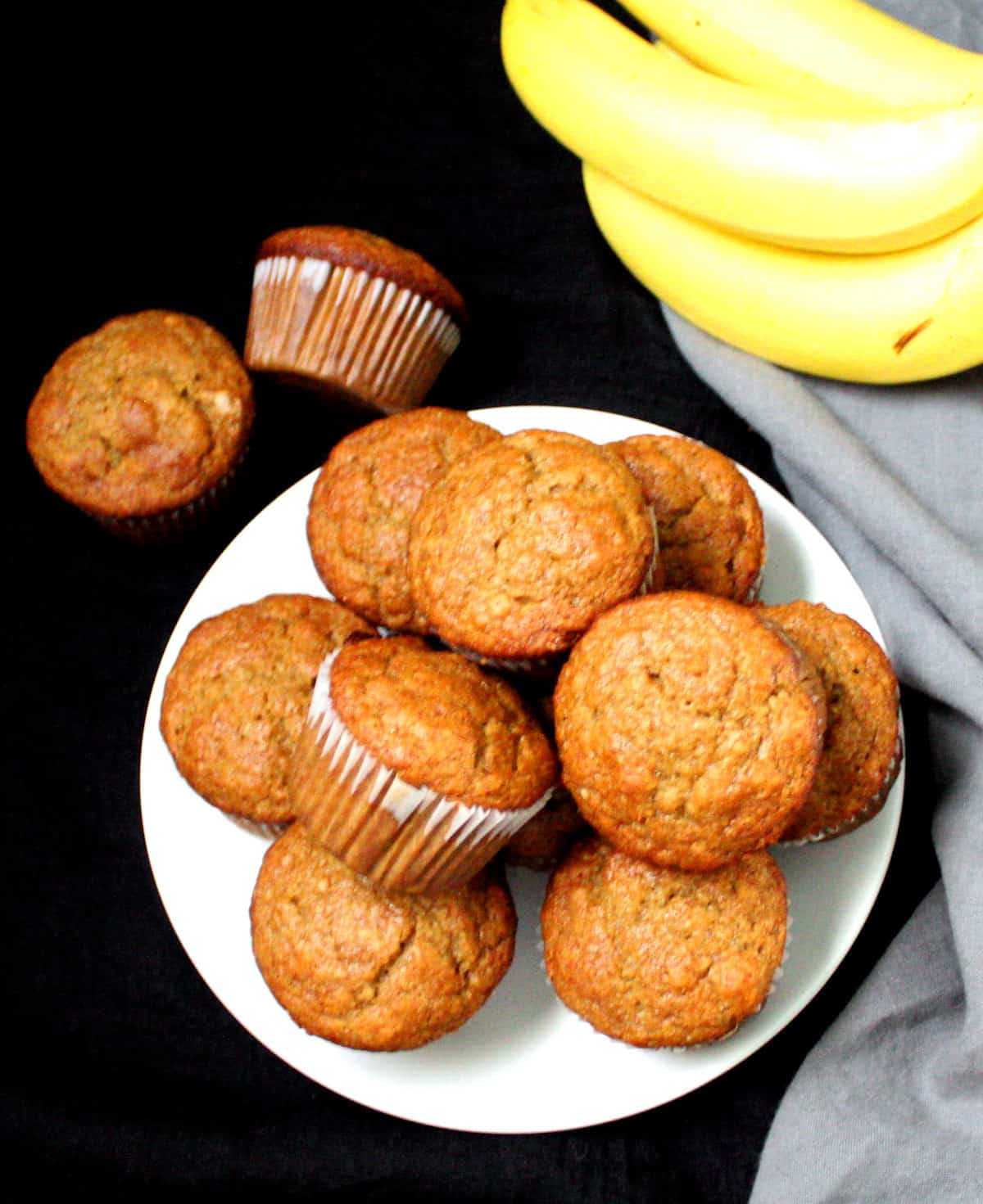 An overhead shot of vegan banana muffins in a white plate with two outside and bananas and a gray napkin.