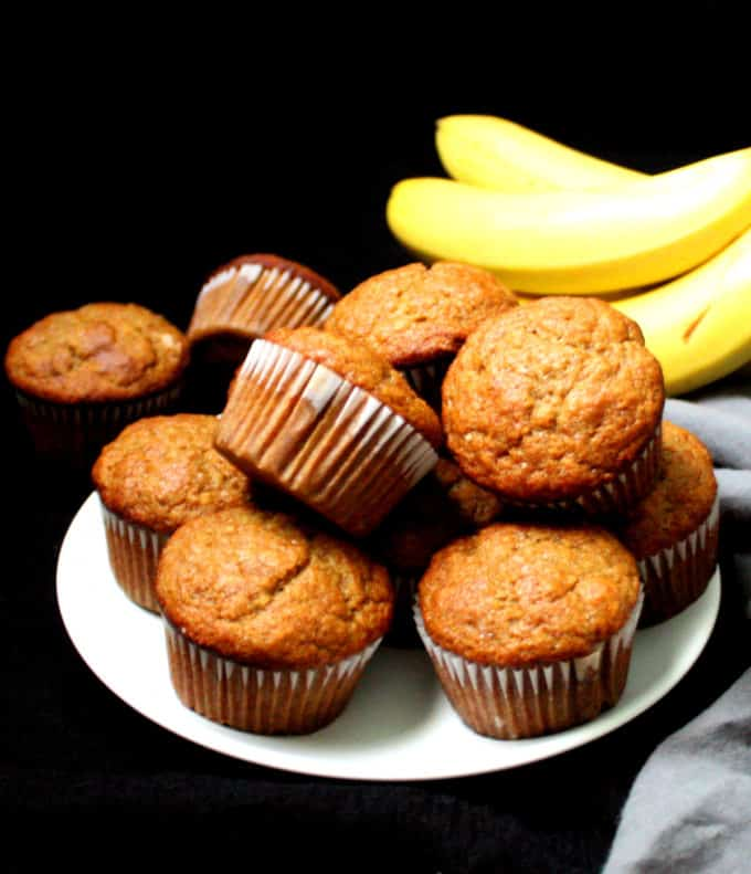 Vegan Banana Muffins stacked on a white plate with ripe bananas in the background.