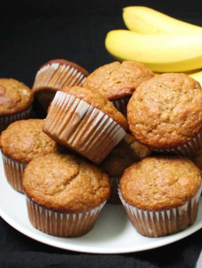Vegan Banana Muffins stacked on a white plate with bananas in the background