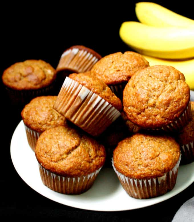 A stack of vegan banana muffins on a white plate with a bunch of yellow bananas in the background.