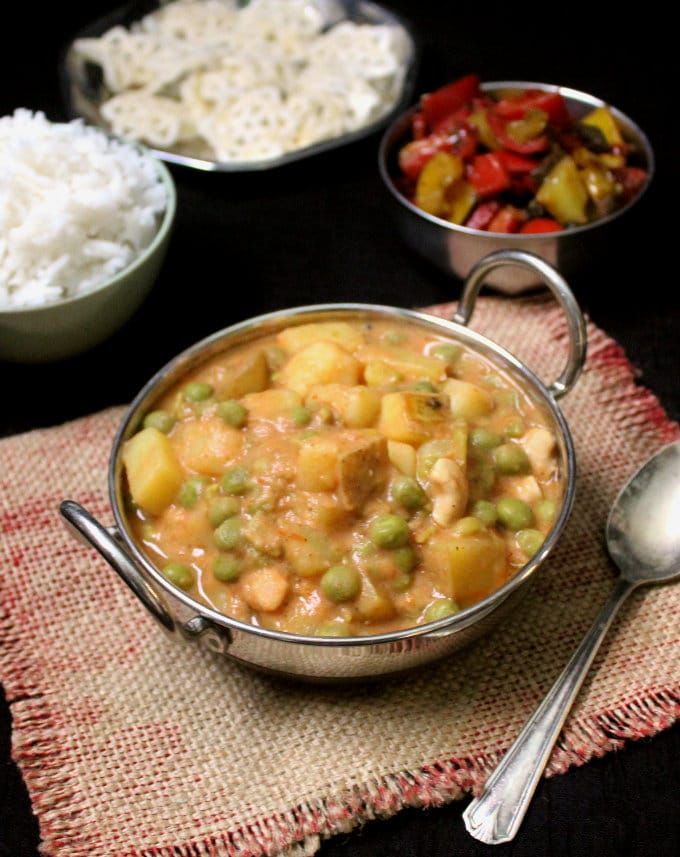 Photo of vegan peas potato curry in a bowl with rice and bell pepper sabzi in the background.
