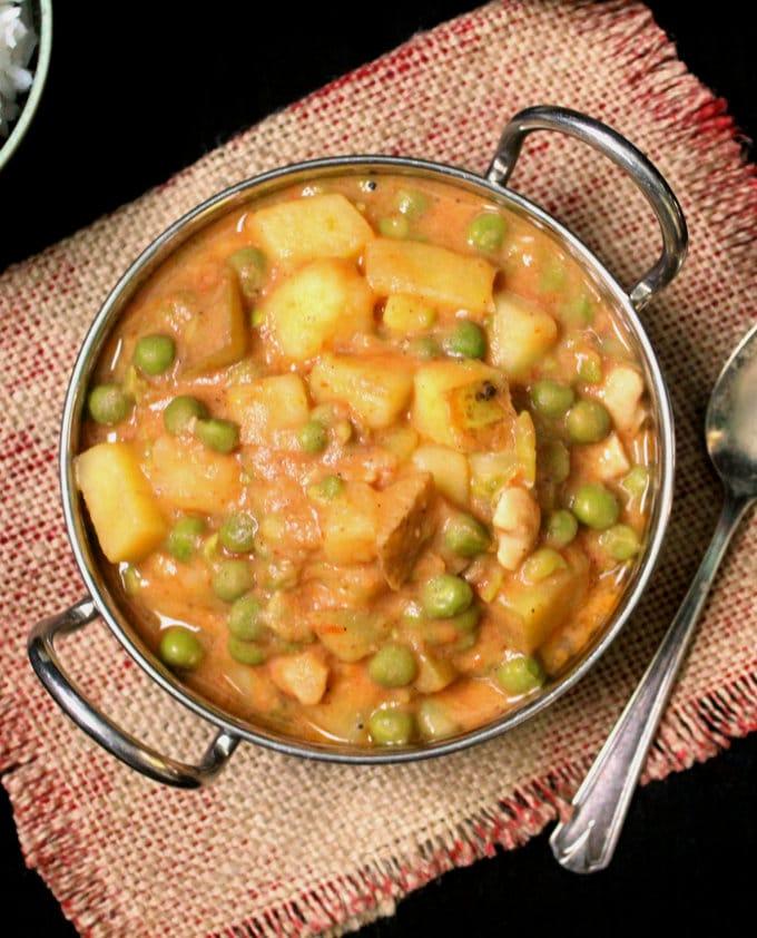 Photo of vegan peas potato curry in a karahi bowl with a spoon.