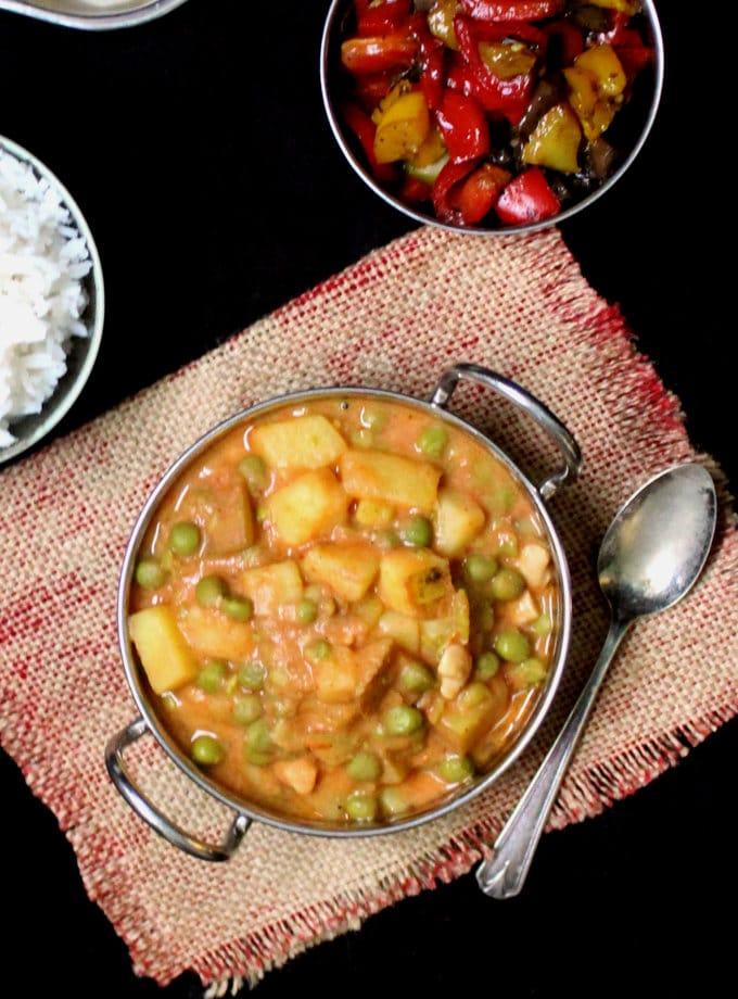 A creamy vegan peas potato curry in a kadhai bowl with a spoon on burlap.