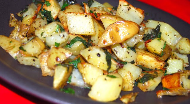 Golden minty roasted potatoes on a black plate