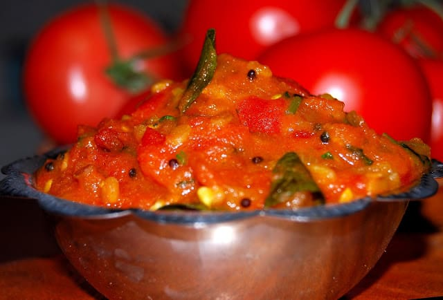 Tomato Chutney made with spices and herbs like curry leaves in a steel bowl