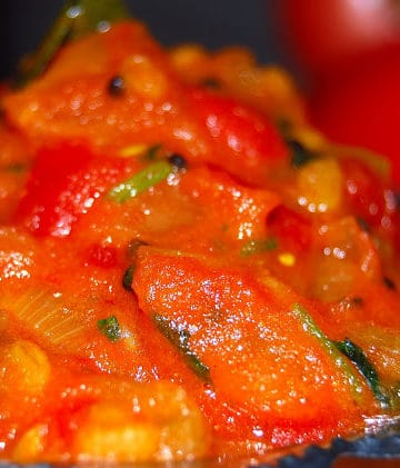 Rich red tomato chutney with spices in a steel bowl
