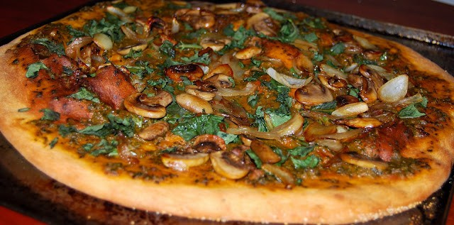 A whole vegan basil pizza topped with mushrooms