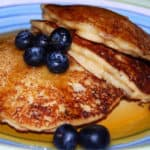 Vegan lemon pancakes with blueberries and maple syrup in a colorful plate