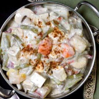 A close up top shot of a bowl of tasty navratan korma, vegan and made with cashew cream