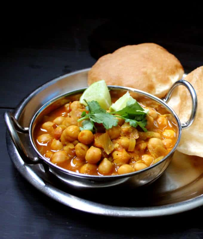 Chole Bhature or Chana Bhatura iserved in a steel karahi with puffy fried breads called bhature and slices of lemon and cilantro.