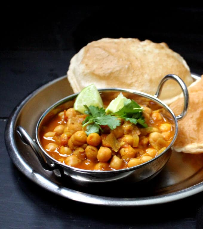 Chole Bhatura or Chana Bhatura in a steel karahi and plate with puffy, fried large puris called bhature.
