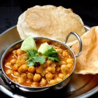 Chole Bhatura or Chana Bhatura is a North Indian dish to die for. A spicy, traditional chana masala is served with a puffy, flaky bread called a Bhatura. You might be lucky enough to find this specialty, usually served at roadside eateries called dhabas in India, at an Indian restaurant. The chana masala is gluten-free. #vegan #soyfree #nutfree #glutenfree #dinner #indian HolyCowVegan.net