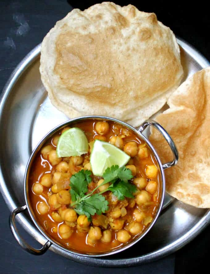 Chole Bhatura served in a steel karahi with puffy breads called bhatura.
