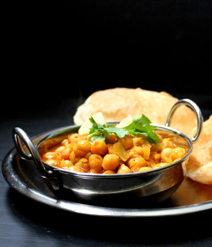 Chole Bhatura or Chana Bhatura in a karahi bowl with puffy bhature.