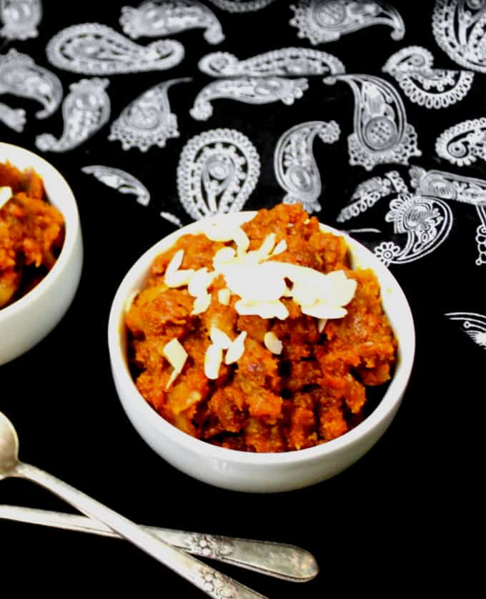A close top shot of a white bowl with gajar ka halwa and sliced almonds with two silver spoons next to it