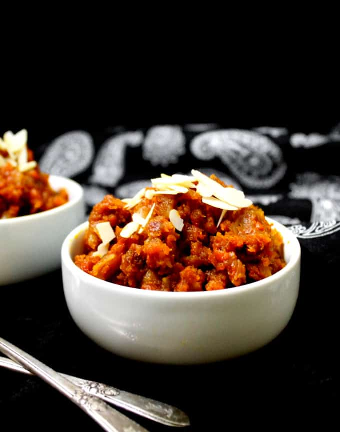 Front shot of a bowl of rich red vegan gajar ka halwa or carrot halwa, an Indian pudding.