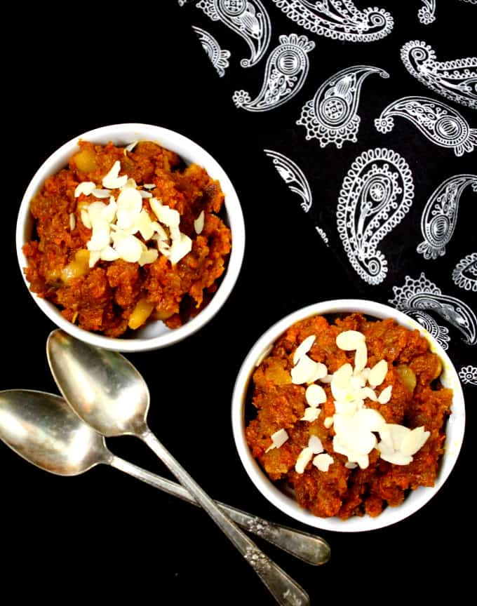 A top shot of two white bowls with orange-red carrot halwa or gajar ka halwa and two silver spoons with a paisley napkin