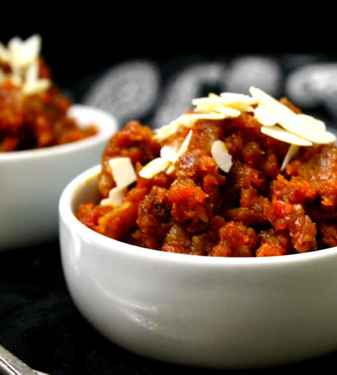Partial shot of a bowl filled with gajar ka halwa and sliced almonds