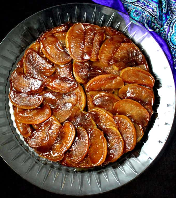 Top short of a glossy vegan Tarte Tatin on a glass crystal plate with blue silk fabric in the background.
