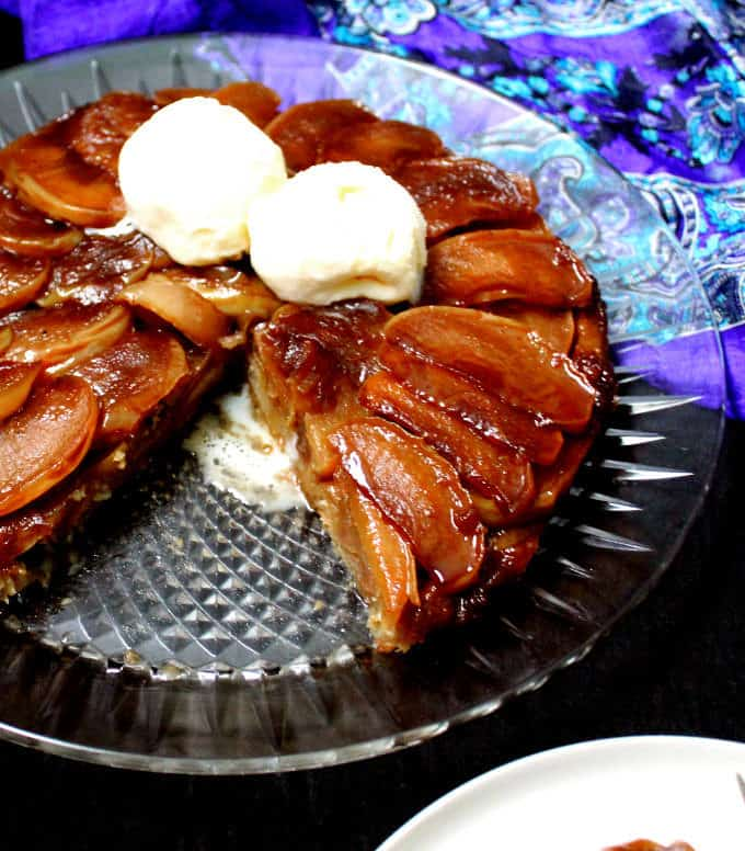 A close up shot of a sliced tarte tatin with scoops of ice cream