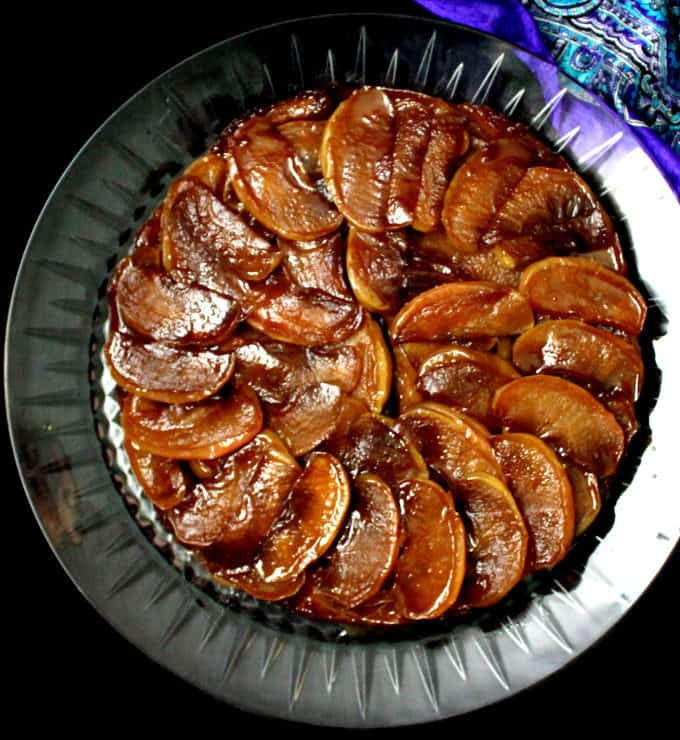 Top shot of a vegan tarte tatin with the amber apple slices arranged in a circular pattern, on a glass platter against a black background