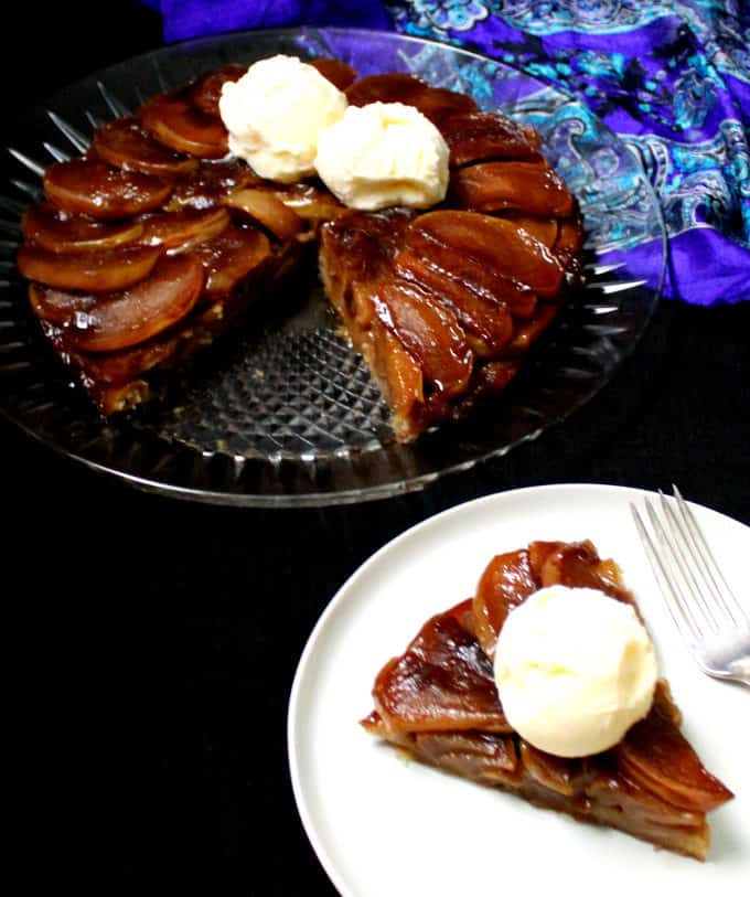 Front shot of a slice of vegan Tarte Tatin with the whole tart in the background on a glass plate with scoops of vegan vanilla ice cream on top